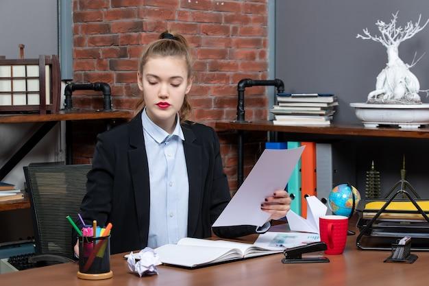 Fiduciosa giovane donna seduta a un tavolo e leggendo i suoi appunti sul taccuino in ufficio