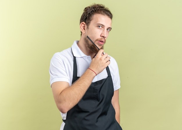 Уверенный молодой мужчина-парикмахер в униформе, расчесывающий бороду расческой, изолированной на оливково-зеленой стене