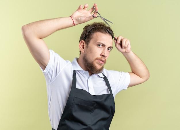 Fiducioso giovane barbiere maschio che indossa l'uniforme tagliando i capelli con le forbici isolate sulla parete verde oliva