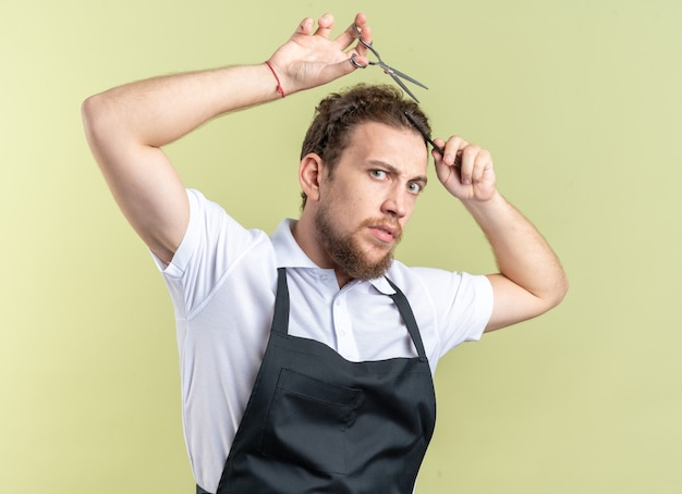 올리브 녹색 벽에 고립 된 가위로 균일 한 절단 머리를 입고 자신감 젊은 남성 이발사