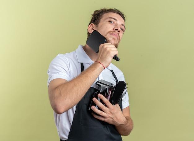 自信を持って若い男性の理髪師は、オリーブグリーンの壁に分離されたひげをとかす理髪ツールを保持している制服を着ています