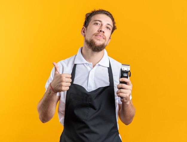 Уверенный молодой мужчина-парикмахер в униформе, держащий машинку для стрижки волос, показывая большой палец вверх, изолированный на желтой стене