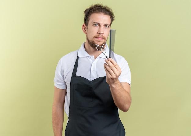 Уверенный молодой мужчина-парикмахер в униформе, протягивая ножницы с гребнем, изолированным на оливково-зеленой стене