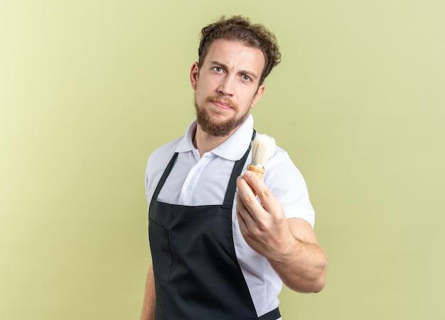 Уверенный молодой мужчина-парикмахер в униформе, протягивая щетку для бритья, изолированную на оливково-зеленой стене