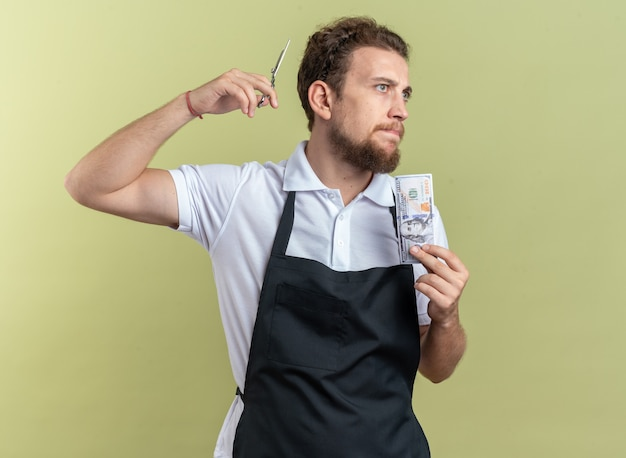 Confident young male barber wearing uniform holding scissors with cash isolated on olive green wall