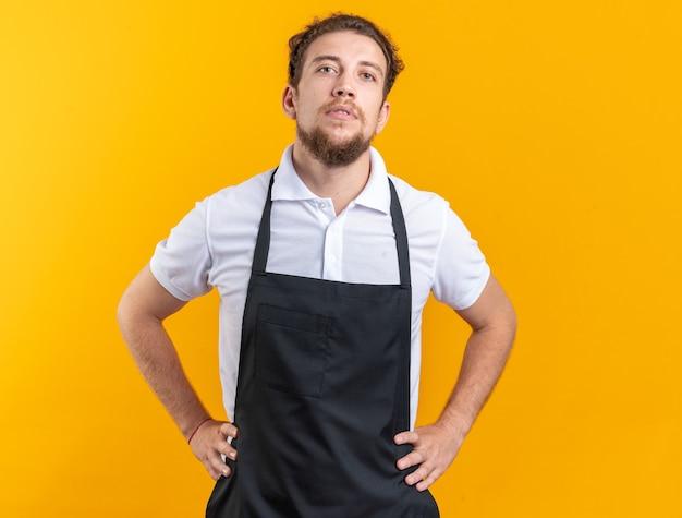Уверенный молодой мужчина-парикмахер в униформе, положив руки на бедро, изолированные на желтой стене