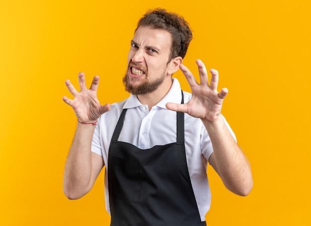 노란색 벽에 고립 된 호랑이 스타일 제스처를 보여주는 유니폼을 입고 자신감이 젊은 남성 이발사