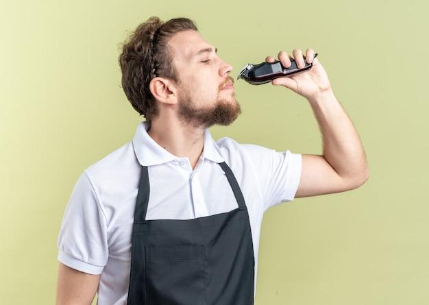 Уверенный молодой мужчина-парикмахер в униформе для стрижки бороды машинкой для стрижки волос, изолированной на оливково-зеленой стене