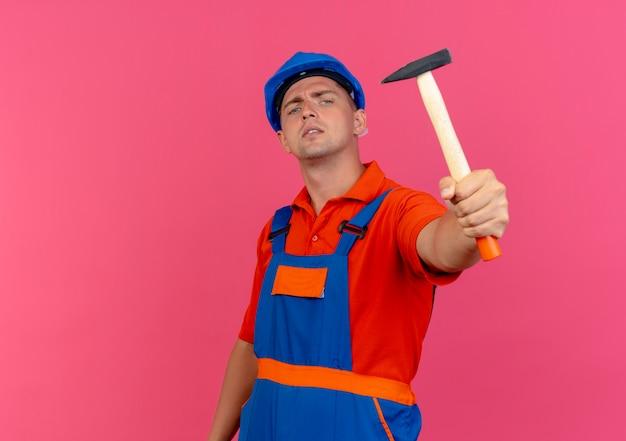 Уверенный молодой мужчина-строитель в униформе и защитном шлеме с молотком