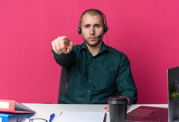 자신감 있는 젊은 남성 콜센터 교환원은 책상에 앉아 몸짓을 보여주는 사무용 도구를 들고 헤드셋을 끼고 있습니다.
