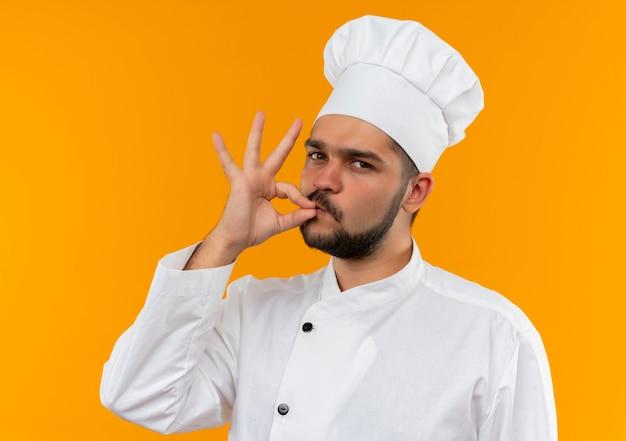 Fiducioso giovane cuoco maschio in uniforme da chef che fa un gesto gustoso isolato sulla parete arancione