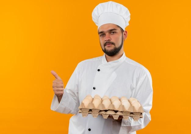 Fiducioso giovane cuoco maschio in uniforme da chef che tiene in mano una scatola di uova e mostra il pollice in alto isolato sulla parete arancione con spazio di copia