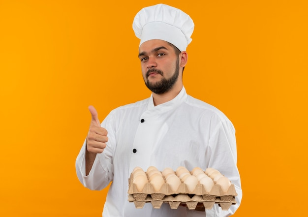 Confident young male cook in chef uniform holding carton of eggs and showing thumb up isolated on orange wall