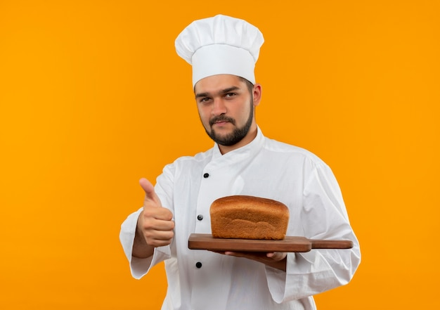 Confident young male cook in chef uniform holding cutting board with bread on it showing thumb up isolated on orange wall