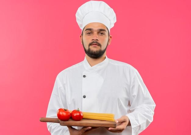 Fiducioso giovane cuoco maschio in uniforme da chef che tiene tagliere con pomodori e pasta di spaghetti su di esso isolato su parete rosa