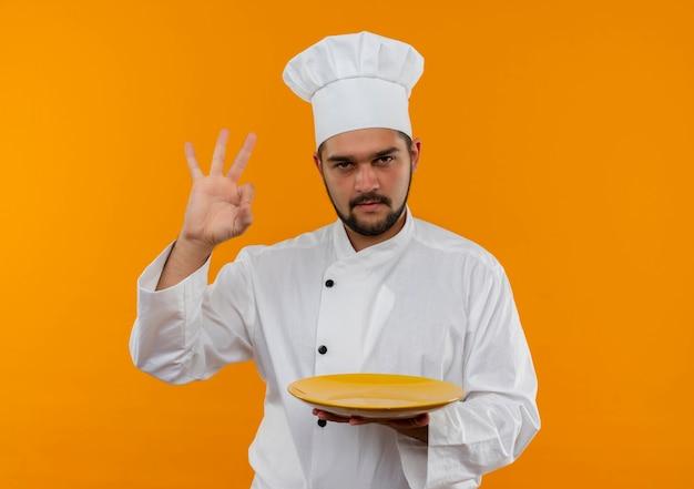 Fiducioso giovane cuoco maschio in uniforme da chef che tiene piatto vuoto e fa segno ok isolato sulla parete arancione con spazio copia
