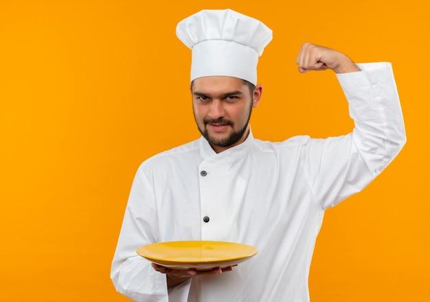 Confident young male cook in chef uniform holding empty plate gesturing strong isolated on orange wall