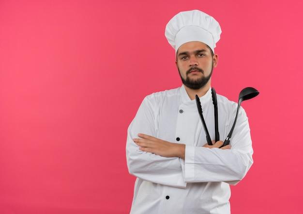 Fiducioso giovane cuoco maschio in uniforme da chef che tiene mestolo e pinze isolate sulla parete rosa con spazio copia