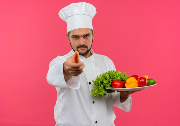 Fiducioso giovane cuoco maschio in uniforme da chef che tiene piatto di verdure e indica con la carota isolata sulla parete rosa con spazio di copia