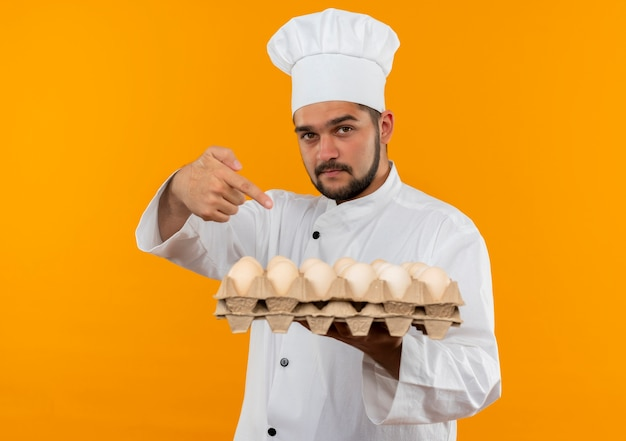 Confident young male cook in chef uniform holding and pointing at carton of eggs isolated on orange wall