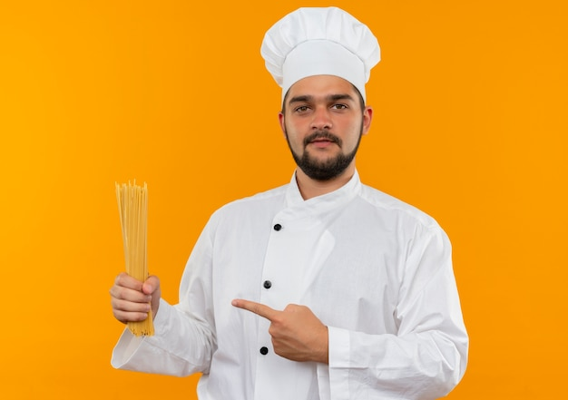 Fiducioso giovane cuoco maschio in uniforme da chef che tiene e indica la pasta degli spaghetti isolata sulla parete arancione