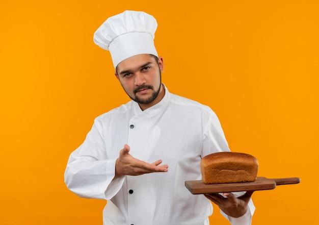 Fiducioso giovane cuoco maschio in uniforme da chef che tiene e indica con la mano il tagliere con pane su di esso isolato su parete arancione