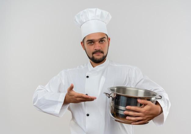 Fiducioso giovane cuoco maschio in uniforme da chef che tiene e indica con la mano la pentola isolata sul muro bianco