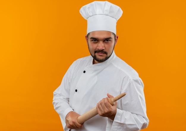 Fiducioso giovane cuoco maschio in uniforme da chef che tiene mattarello guardando isolato sulla parete arancione con spazio di copia
