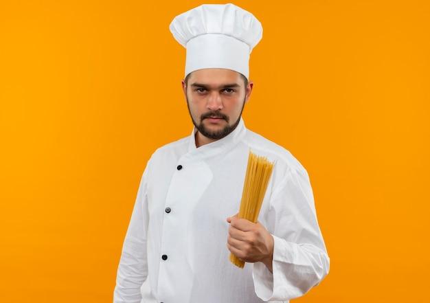 Fiducioso giovane cuoco maschio in uniforme da chef che tiene pasta di spaghetti isolata sulla parete arancione con spazio di copia