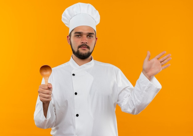 Confident young male cook in chef uniform holding spoon and showing empty hand isolated on orange wall