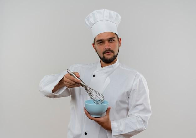 Fiducioso giovane cuoco maschio in uniforme da chef che tiene in mano una frusta e una ciotola che sembrano isolate sul muro bianco con spazio di copia