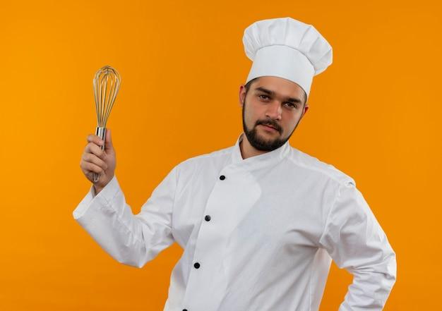 Fiducioso giovane cuoco maschio in uniforme da chef tenendo la frusta isolata sulla parete arancione on