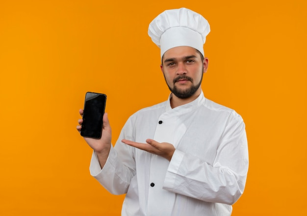 Fiducioso giovane cuoco maschio in uniforme da chef che mostra e indica con la mano il telefono cellulare isolato sulla parete arancione