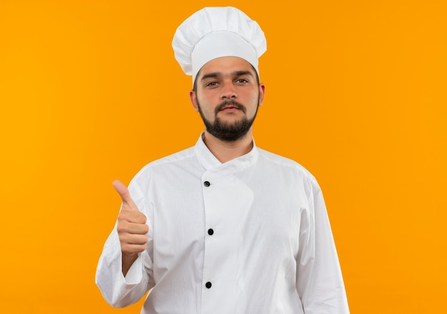 Confident young male cook in chef uniform showing thumb up isolated on orange wall
