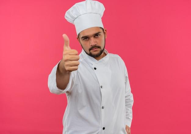Fiducioso giovane cuoco maschio in uniforme da chef che mostra pollice in su isolato sulla parete rosa con spazio di copia
