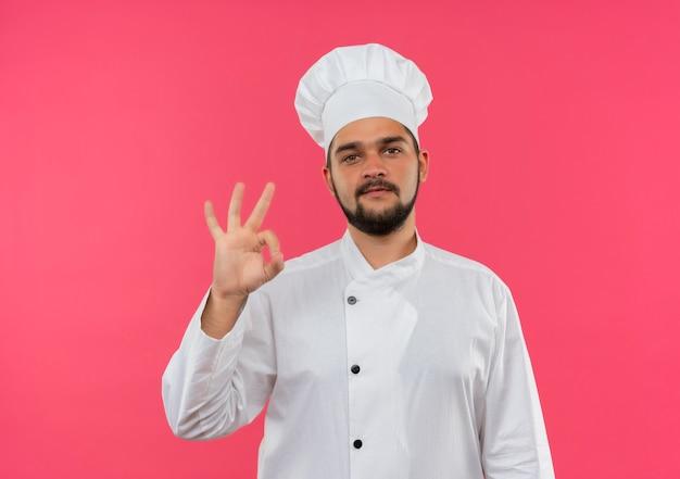 Уверенный молодой мужчина-повар в униформе шеф-повара делает знак ок на розовой стене с копией пространства