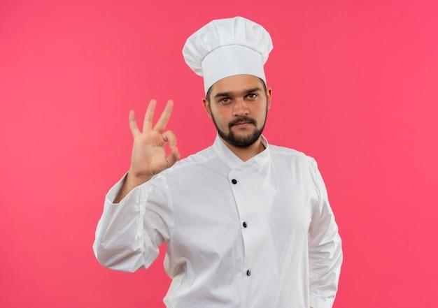 Уверенный молодой мужчина-повар в униформе шеф-повара делает знак ок на розовой стене