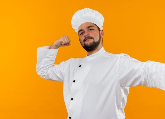 Уверенный молодой мужчина-повар в униформе шеф-повара жестко жестикулирует изолированно на оранжевой стене