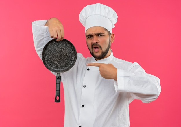 Уверенный молодой мужчина-повар в униформе шеф-повара держит и указывает на сковороду, изолированную на розовой стене