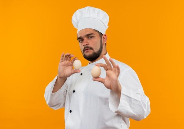 オレンジ色の壁に卵を持ったシェフの制服を着た自信のある若い男性料理人