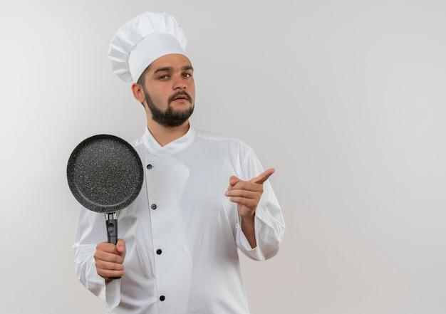 シェフの制服を着た自信に満ちた若い男性料理人がフライパンを持ち、コピースペースのある白い壁に真っ直ぐ指している