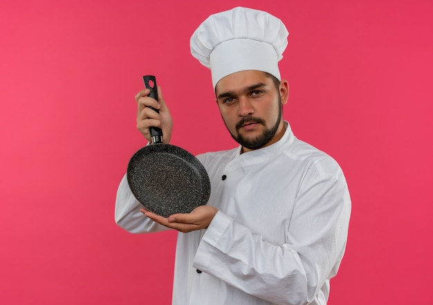 コピー スペースでピンクの壁に分離されたフライパンを保持しているシェフの制服を着た自信のある若い男性料理人