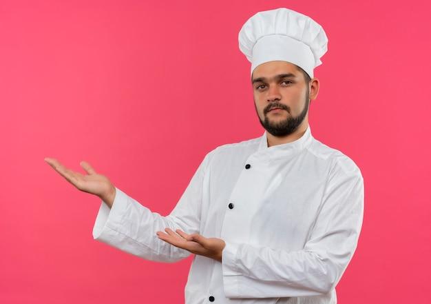 분홍색 벽에 고립 된 측면에서 손으로 가리키는 요리사 유니폼에 자신감이 젊은 남성 요리사