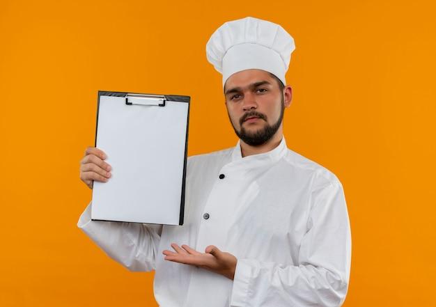 Уверенный молодой мужчина-повар в униформе шеф-повара показывает и указывает рукой на буфер обмена, изолированный на оранжевой стене
