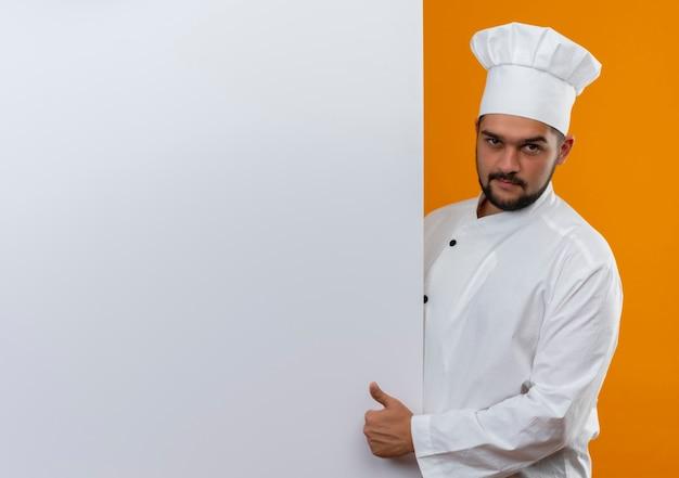 白い壁の後ろに立つシェフの制服を着た自信のある若い男性料理人が、コピースペースのあるオレンジ色の壁に孤立して見える親指を現す