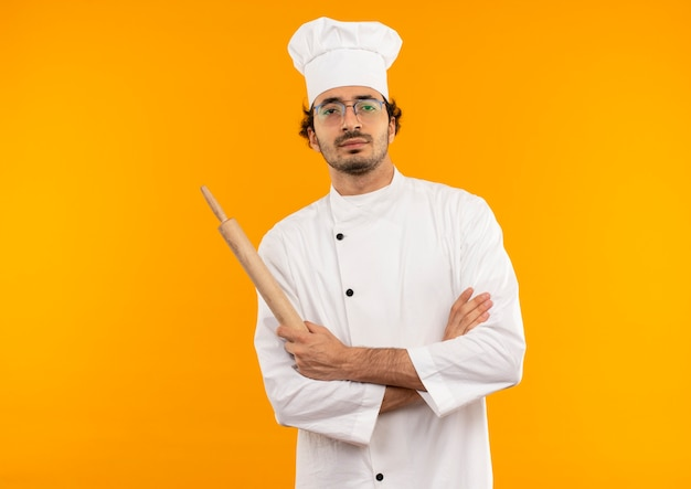 자신감이 젊은 남성 요리사 요리사 유니폼을 입고 안경 손을 건너와 롤링 핀을 잡고