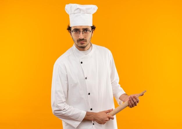 요리사 유니폼과 롤링 핀을 들고 안경을 착용 확신 젊은 남성 요리사