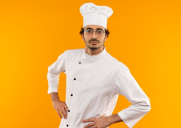 シェフの制服と腰に手を置く眼鏡を身に着けている自信を持って若い男性料理人
