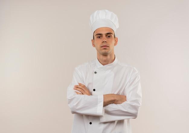 Fiducioso giovane cuoco maschio che indossa chef uniforme crosing mani sulla parete bianca isolata con lo spazio della copia
