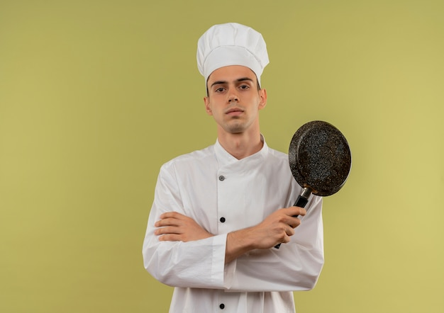 コピースペースのある孤立した緑の壁にフライパンを持ってシェフの制服を着て自信を持って若い男性料理人